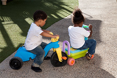 Two young children riding colorful toy cycles